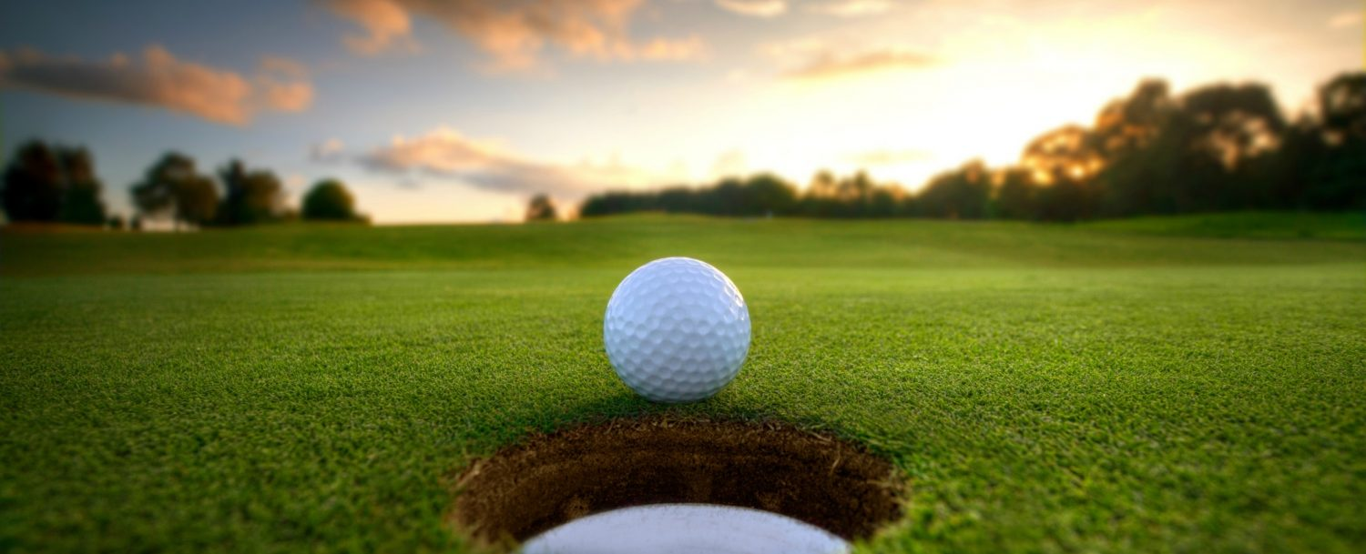 golf ball rolling into hole on course with sunset background