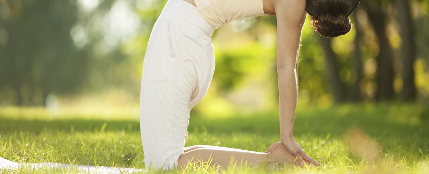 woman doing yoga in the grassy hills