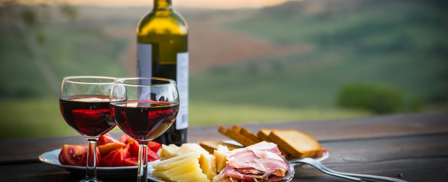 wine glasses and bottle with meat and cheese tray overlooking vineyard