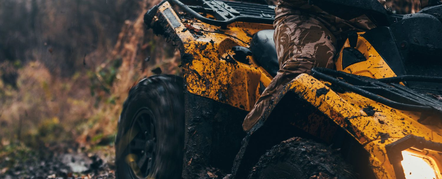 Man in camp riding on a muddy yellow ATV.