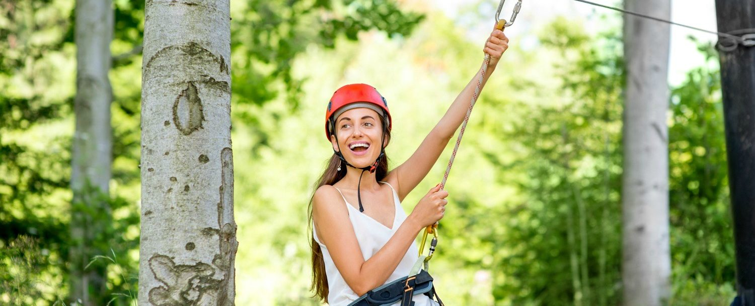happy young woman in red helmet riding on a zip line in the forest