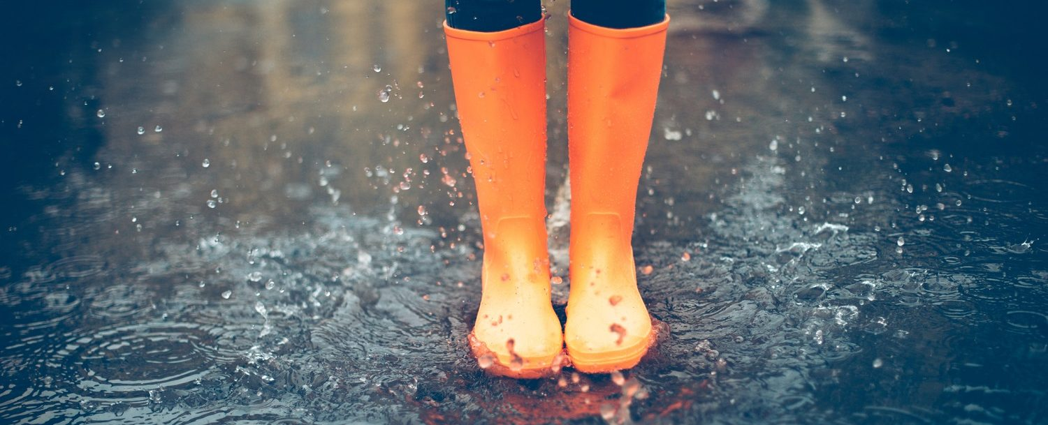 Close-up of woman in orange rubber boots jumping on a puddle