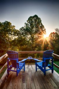 Adirondack chairs on balcony overlooking trees and sunset
