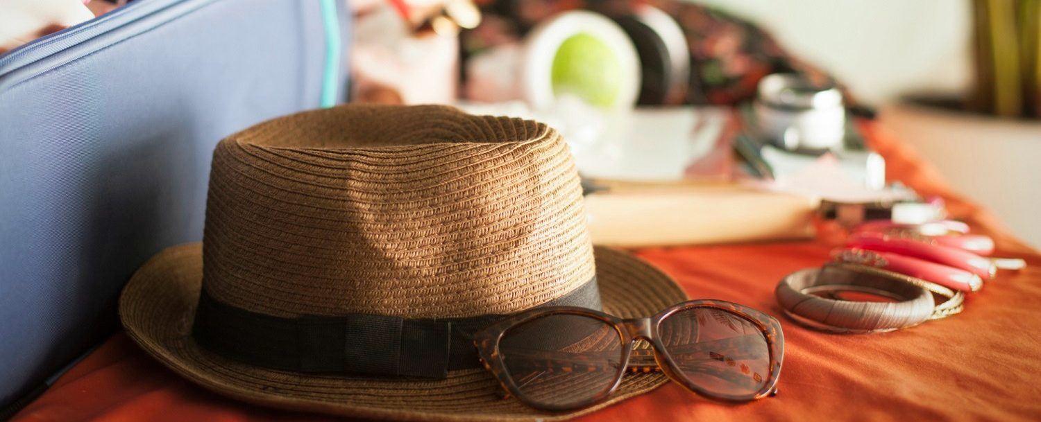 hat and sunglasses being packed for vacation