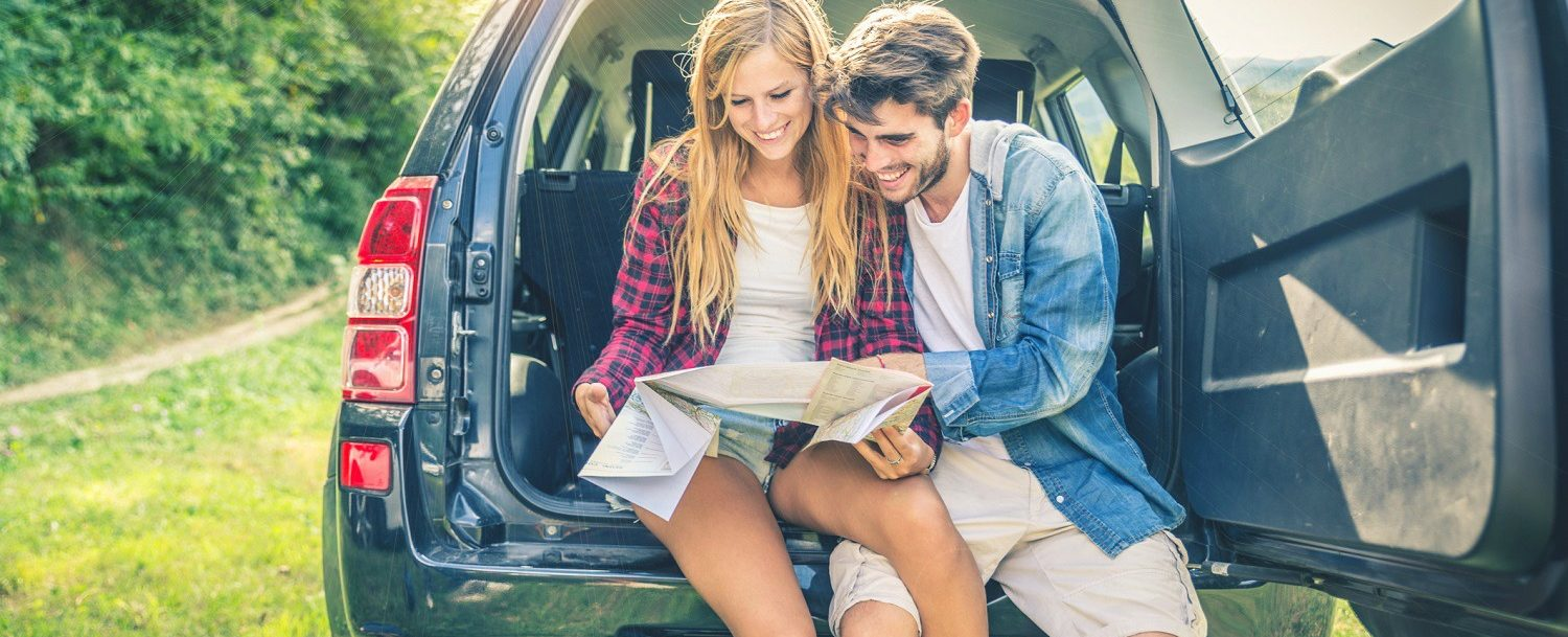 young couple looking at map on road trip
