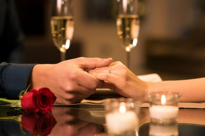 couple holding hands across table with rose and champagne