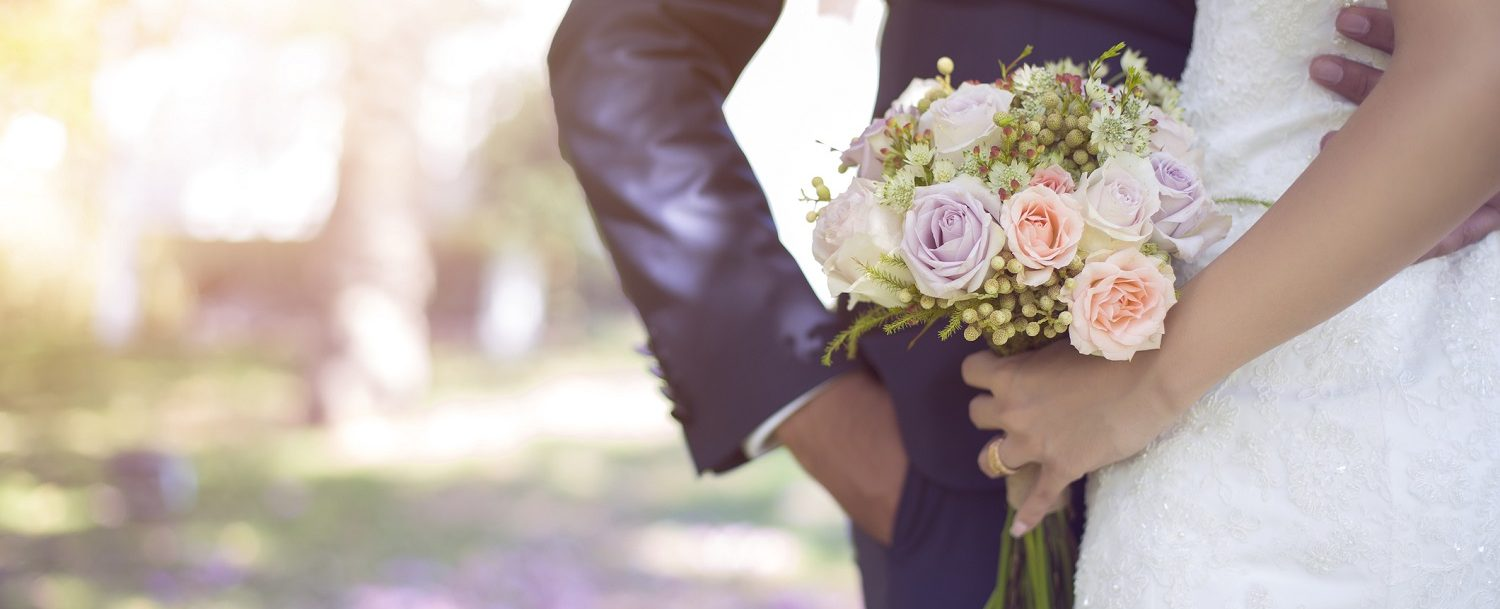 bride holding bouquet with groom's arm around her waist