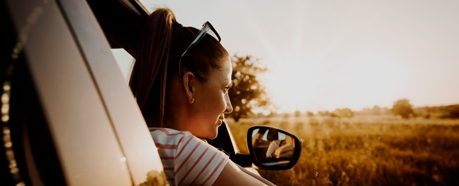 Woman looking out the window of a car on a road trip.