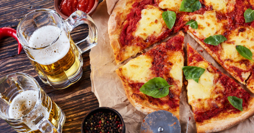 Pizza and beer on a table.
