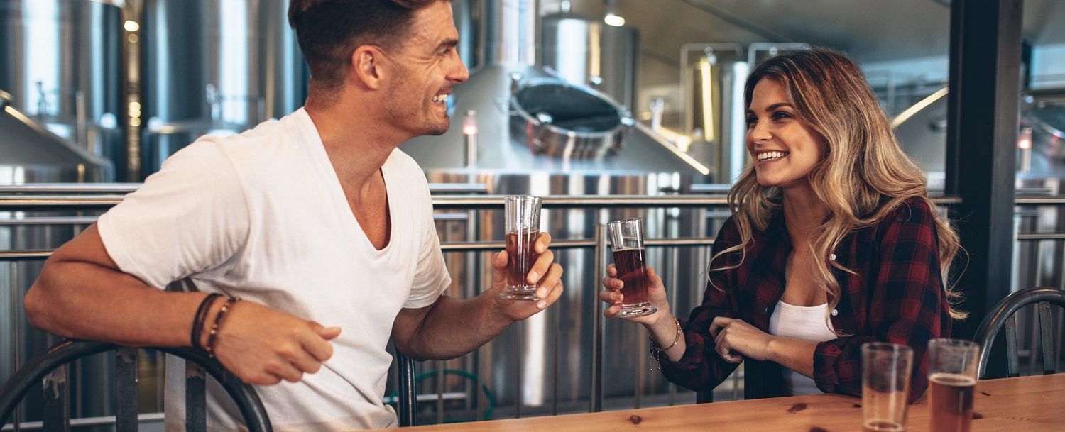 Couple at brewery toasting beers. Young man and woman tasting different varieties of craft beers.