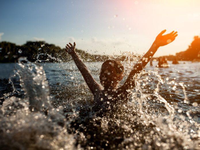 child splashing around in a lake