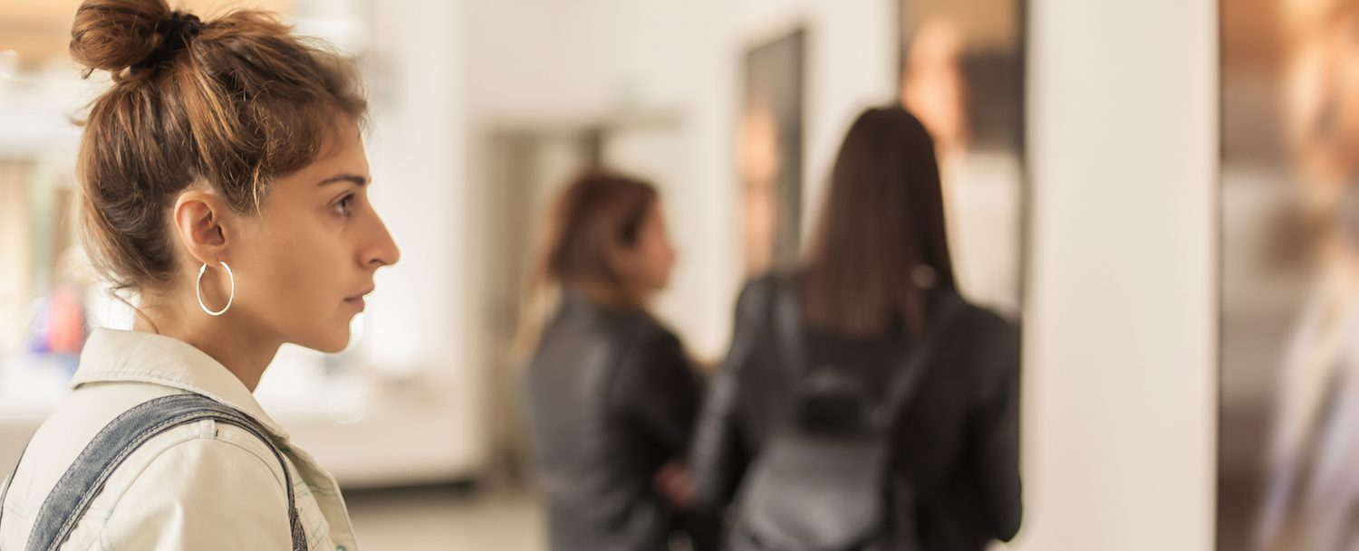 Woman looking at a painting in an art gallery.