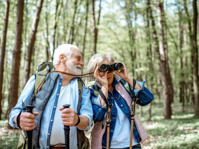 Older couple hiking through the woods birdwatching.