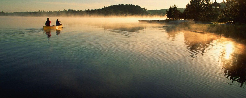 Couple canoeing on lake at sunset.