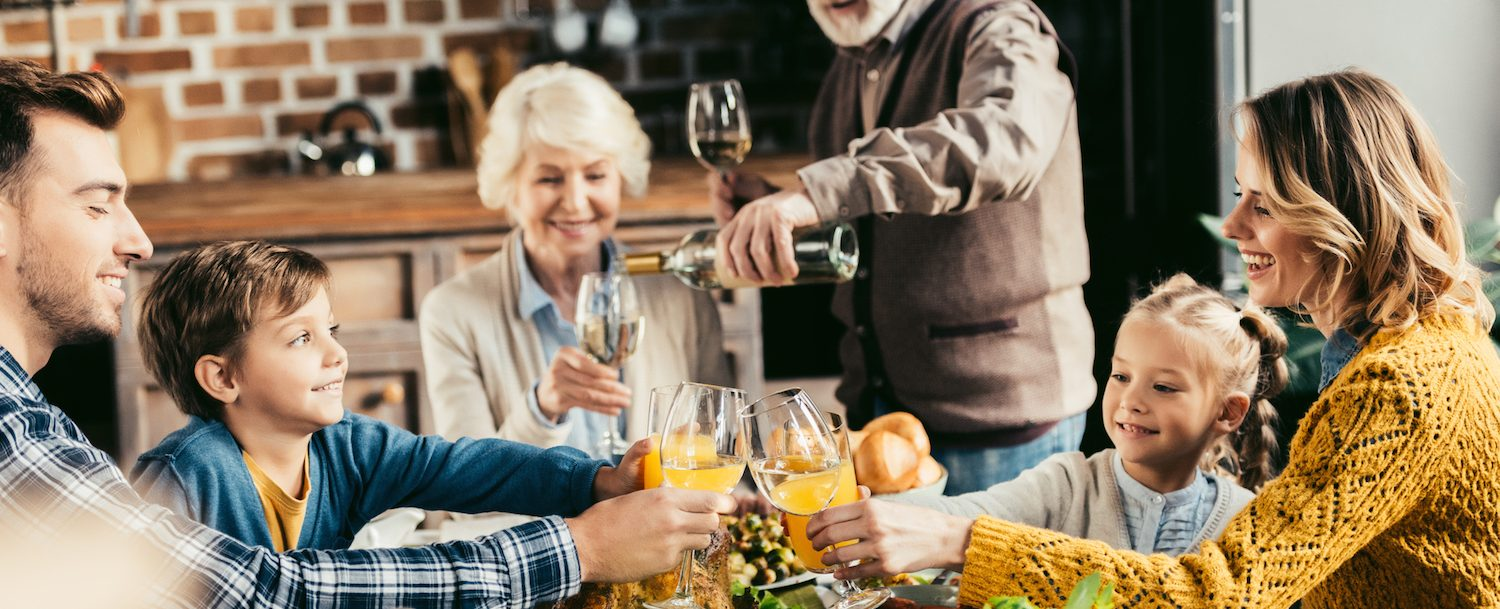 beautiful family clinking glasses of wine and juice on holiday dinner