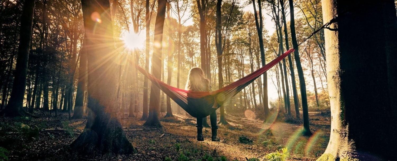 Woman sitting in hammock in the woods.