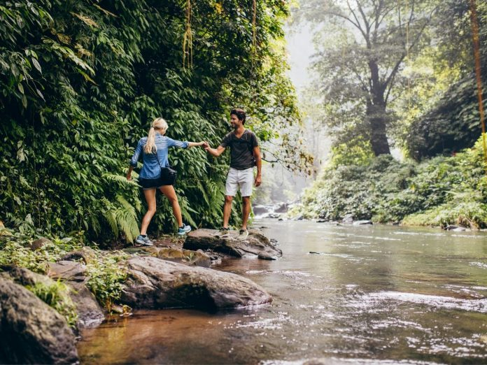 Couple hiking through the forest near a stream.